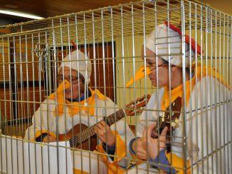 Frauen stellen gefangene Hühner dar und singen